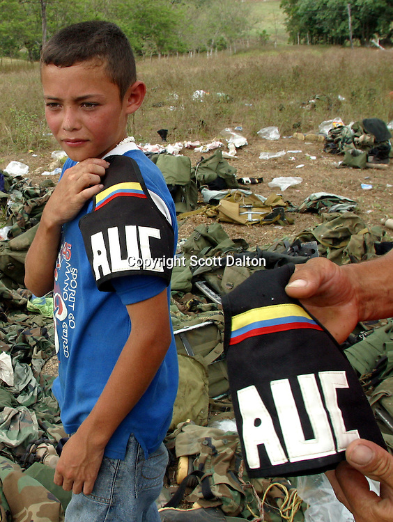 A young boy tries on an armband that was left behind after the disarmament ceremony of the paramilitary group Bloque Norte, or Northern Block, in Chimila, in northern Colombia on March 8, 2006. An estimated 24,000 paramilitary members have turned in their weapons as part of a government negotiated peace deal. But some are skeptical if the government plan will really work and if the paramilitary members will be successful in their transformation to civilian life. (Photo/Scott Dalton)