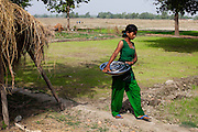Pramila Tharu, 15, does household chores as other children go to school in Bhaishahi village, Bardia, Western Nepal, on 29th June 2012. Pramila eloped and married at 12 and gave birth to Prapti at age 13. She delivered prematurely on the way to the hospital in an ox cart and her baby weighed only 1.5kg at birth. In Bardia, StC works with the district health office to build the capacity of female community health workers who are on the frontline of health service provision like ante-natal and post-natal care, especially in rural areas. Photo by Suzanne Lee for Save The Children UK
