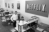 Reed Hastings, left, CEO and Co-founder of Netflix, speaks with employees at the new Phoenixville, Pennsylvania distribution center, Wednesday, February 12, 2003, in Phoenixville, Pennsylvania. Netflix plans to open one to two facilities per month for the remainder of 2003 as part of its ongoing strategy to provide one-day movie delivery to its members. By year-end 2003, Netflix expects that it will be able to reach more than 70 percent of its subscribers with generally next-day service. (Photo by William Thomas Cain)