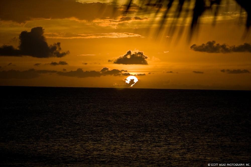 Sun setting in an orange sky over Maui, Hawaii