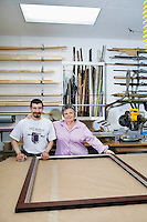 Portrait of happy senior owner with mature employee in frame workshop