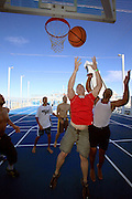 Passengers playing on the basketball court onboard the cruise ship Oasis of the Seas. The ship, currently the largest in the world, is owned by Royal Carribean Cruise Line.