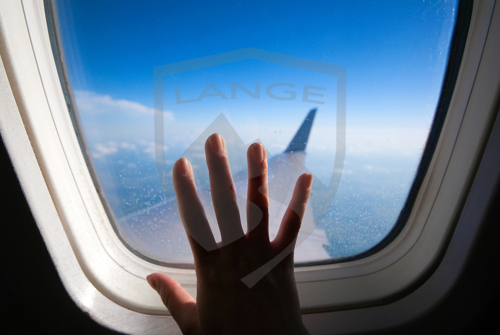 airplane window with hand pressed against glass.