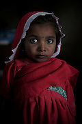A portrait of Bhagli Bheel, age 4, was enslaved with the rest of her family.<br /> <br /> Following the release of the Global Slavery Index by the Walk Free Foundation Pakistan is ranked 3rd worse in the world behind India and China. The Asian Development Bank estimates some 1.8 million people are slaves in Pakistan yet other estimates reach up to 4 million people, most of which toil year after year in brick kilns or sugar cane plantations. Their stories are the same; they have no-where to turn so they borrow money from a land-owner for a medical emergency or marriage dowry. The landlords pay in return for work, their labour supposed to be taken off the amount borrowed. Yet after years of no salary incredibly their amount owed is often quadrupled, the excuse being the amount they cost to feed! Many are chained, abused, raped and even killed.<br /> <br /> For years they had no where to run, no one to help but now a small local NGO called the Green Development Rural Organisation (GDRO) works to free bonded-slaves by using the law against their captives. Yet, often freed slaves end up right back where they were or risk being hunted by the landowner and forced to return. So GRDO started building villages so slaves who escape or are freed have somewhere safe to go. It now has two, whose names translate from Urdu as 'Village of the Freed' and 'Village of the Courageous', and is working on a 3rd. The land is bought and allocated to freed slave families where they can built a house and start again. Without such help the vicious cycle would continue.