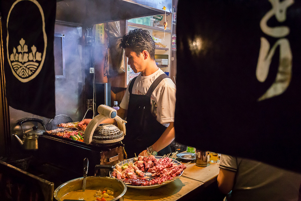 The cook of one of the small restaurants in Omoide Yokocho (or Yakitori Alley) grills the small kebabs known as yakitori.