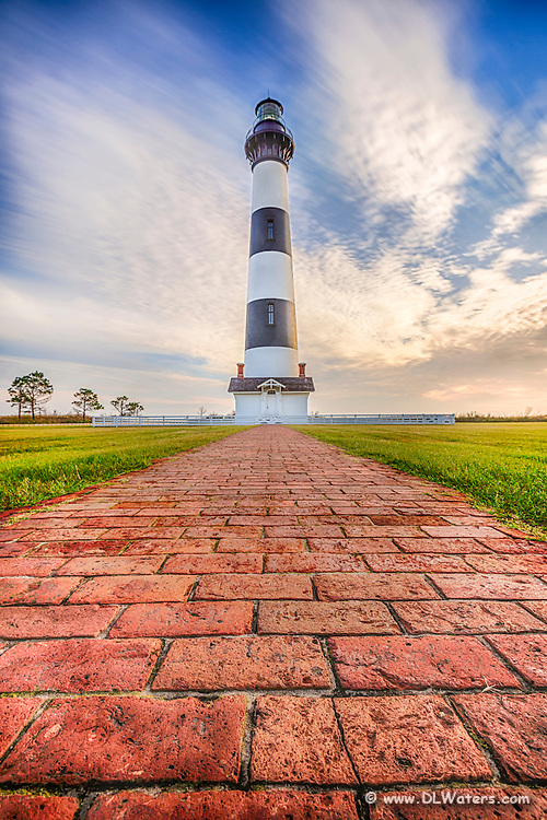 A low perspective of Bodie Island Lighthouse with sweeping clouds moving during a long exposure.