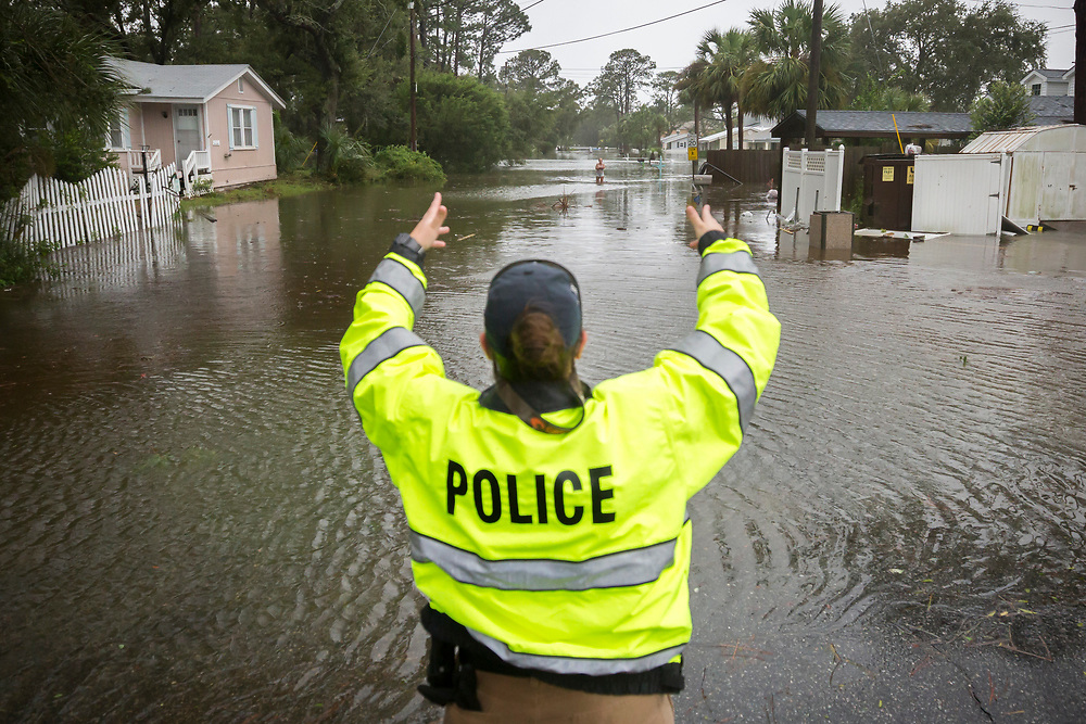 A City of Tybee police officer checks the well being of a resident fleeing her flooded home on Tybee Island, Ga., Monday, Sept., 11, 2017. Parts of the coastal Georgia island suffered storm surge from Tropical Storm Irma. (AP Photo/Stephen B. Morton)