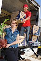Portrait of woman unloading with worker truck of cardboard boxes