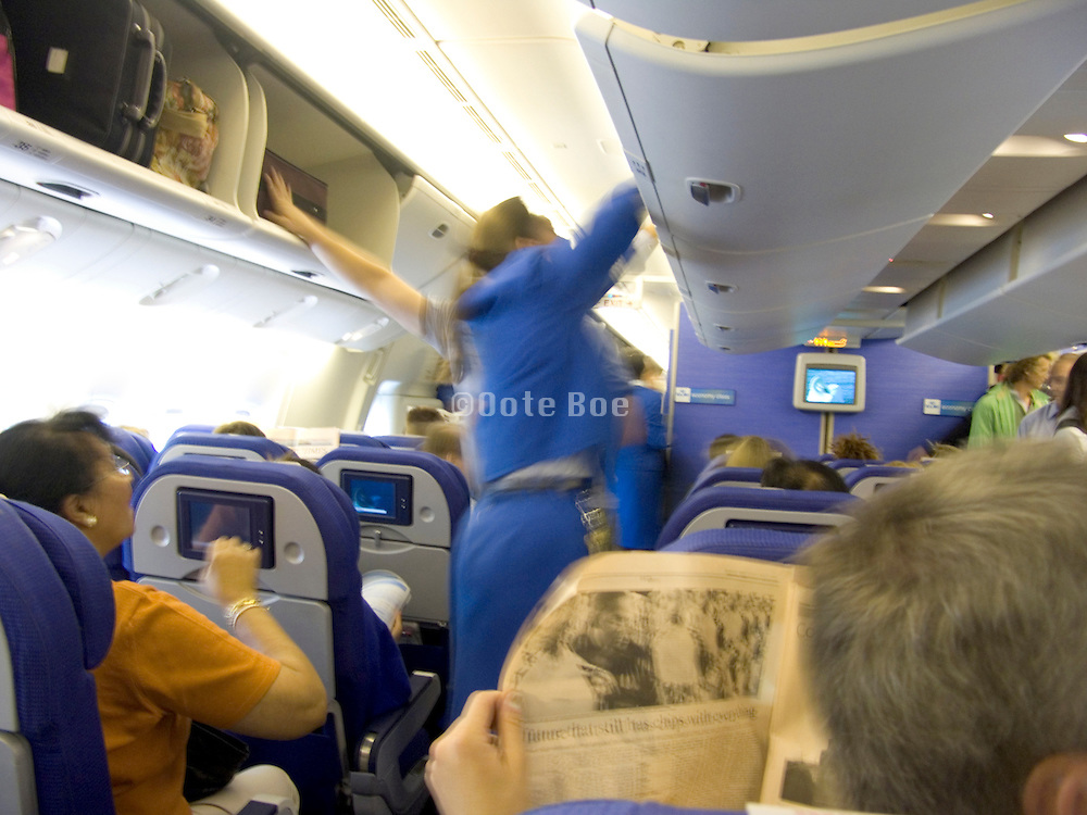 stewardess helping to store luggage in overhead cabin