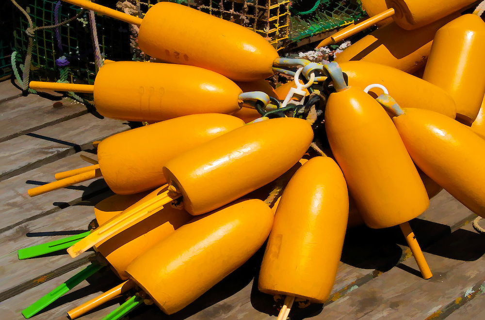 Bright yellow lobster buoys on a dock in Port Clyde, Maine wiht lobster traps.