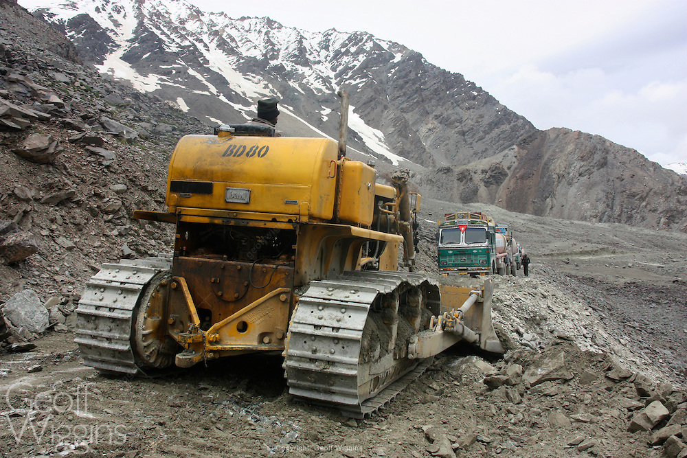 Indian bulldozer clears landslide as truck convoy waits near the treacherous Barachla pass, Ladakh, India