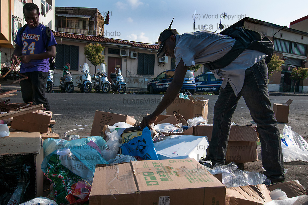 profughi libici cercano cose nella spazzatura da vendere al mercato abusivo alle spalle di piazza Garibaldi, Napoli;<br />