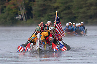 A voyageur canoe sponsored by Campmor, an outdoor recreation equipment store in New Jersey, paddles on Fish Creek Pond during day three of the Adirondack Canoe Classic (90-Miler).