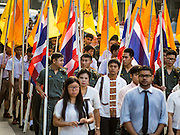 30 OCTOBER 2014 - BANGKOK, THAILAND: Thai university students march down Bamrung Muang Street during the parade marking the start of the annual temple fair at Wat Saket. Wat Saket is on a man-made hill in the historic section of Bangkok. The temple has golden spire that is 260 feet high which was the highest point in Bangkok for more than 100 years. The temple construction began in the 1800s in the reign of King Rama III and was completed in the reign of King Rama IV. The annual temple fair is held on the 12th lunar month, for nine days around the November full moon. During the fair a red cloth (reminiscent of a monk's robe) is placed around the Golden Mount while the temple grounds hosts Thai traditional theatre, food stalls and traditional shows.   PHOTO BY JACK KURTZ