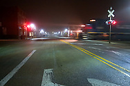 Passing westbound over the quiet streets of Gilman, IL, a TP&W freight train crosses Main Street around 2am.
