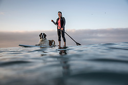 Abigail Convery and her Saint Bernard puppy Olive paddle board on Ventura beach at sunrise, October 12, 2014