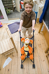 Little boy playing with his teddy in a pushchair,