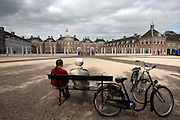 Twee oudere fietsers zitten op een bankje voor paleis het Loo in Apeldoorn.<br /> <br /> A couple is resting with their bikes at the palace Het Loo in Apeldoorn.