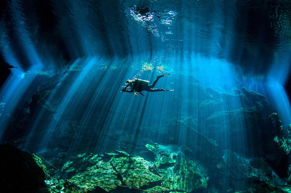 Scuba diver exploring the Chuk-Mool Cenote on the Mayan Riviera.