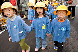 Asia, Japan, Gifu prefecture, Takayama (also known as Hida-Takayama), children in uniforms and yellow hats holding hands while walking on a school field trip to a market