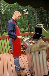 Food suburban man male cooks hot dogs hamburgers on  backyard bbq grill