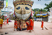 29 JUNE 2014 - DAN SAI, LOEI, THAILAND: Buddhist monks and novices put away a parade float after the Ghost Festival in Dan Sai. Phi Ta Khon (also spelled Pee Ta Khon) is the Ghost Festival. Over three days, the town's residents invite protection from Phra U-pakut, the spirit that lives in the Mun River, which runs through Dan Sai. People in the town and surrounding villages wear costumes made of patchwork and ornate masks and are thought be ghosts who were awoken from the dead when Vessantra Jataka (one of the Buddhas) came out of the forest. On the last day of the festival people participate in merit making ceremonies at the Wat Ponchai in Dan Sai and lead processions through town soliciting donations for the temple.    PHOTO BY JACK KURTZ