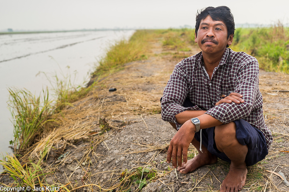 17 MARCH 2014 - BUNG KHAM PROI, PATHUM THANI, THAILAND: A farm worker sits on the edge of a rice field he works in. He said his fields are one of the few in the area that still have water because they are lower than surrounding fields. He said he provides some water to neighboring farmers. It hasn't rained in central Thailand in more than three months, impacting agriculture and domestic water use. Many farms are running short of irrigration water and salt water from the Gulf of Siam has come up the Chao Phraya River and infiltrated the water plants in Pathum Thani province that serve Bangkok. PHOTO BY JACK KURTZ