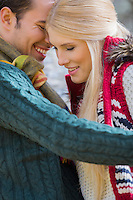 Romantic young couple in sweaters smiling at park