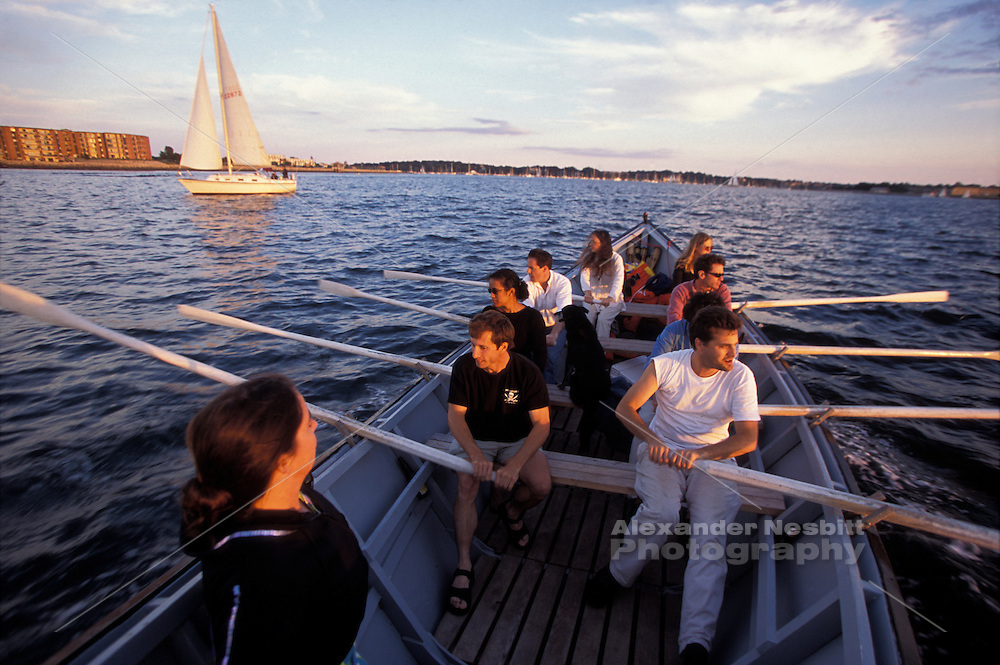 Newport, RI - Group rows a large wooden row boat in Narragansett bay near Newport and Goat Island.