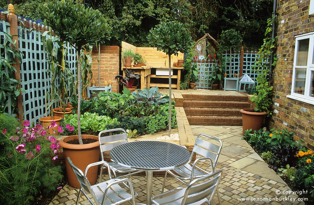 Paved kitchen garden with changing levels. Table and chairs, raised vegetable bed with outdoor kitchen in the distance. Standard bay trees.