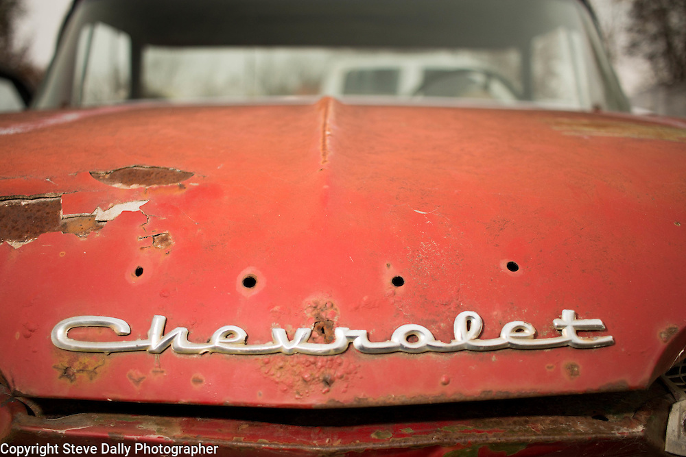 Chrome Chevrolet hood ornament, name plate.<br /> Red sedan, 1950s