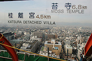 Looking out from the observation deck of Kyoto Tower towards the cultural sights of the city (indicated by signs on the glass window), Kyoto, Japan, on Tuesday, Jan. 16, 2007.