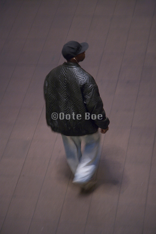 an overhead view of a teenaged boy walking alone