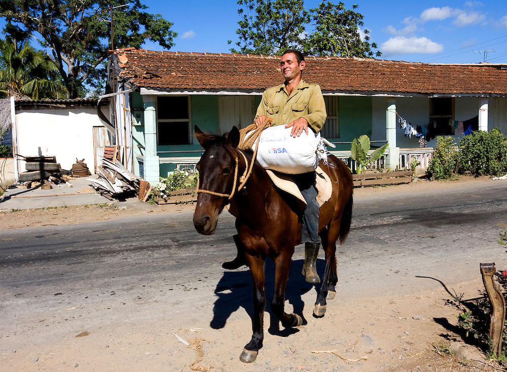 Man on horse with a sack in Puente de Cabezas, Pinar del Rio, Cuba.