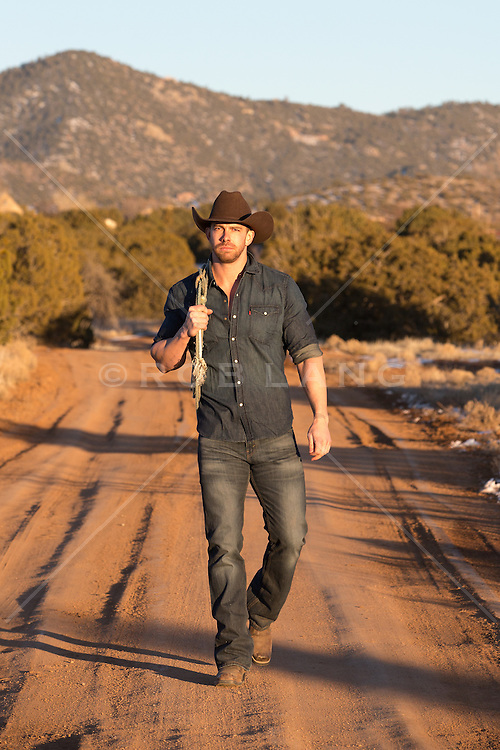 rugged cowboy with a lasso walking on a dirt road at sunset