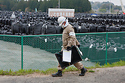 A decontamination worker walks past a depot piled with large vinyl bags icontaing topsoil that has been removed, near Nahara, Fukushima, Japan. Tuesday April 30th 2013 The Japanese government has decided to remove the topsoil and vegetation from the areas affected by radiation after the disaster at Fukushima Daichi nuclear plant on March 11th 2011