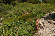 Two year baby boy plays alone by a small water stream