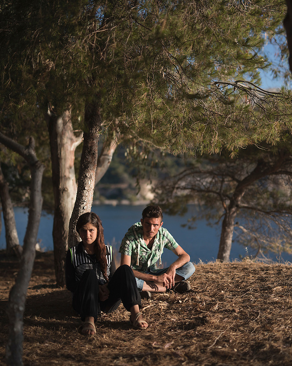 Yazidi refugees Hazim Elias Khadeda, 22, and his sister Leena Elias Khadeda, 16, sit among the pines beside the sea at Lakki.