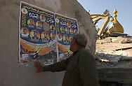 Al Zaytoun, Gaza.   Mohammed Abu Ali, checks on a poster, the names of martyrs in the wall of a destroyed mosque in the neighborhood of Al Zaytoun in Gaza. The martyrs were killed by the Israel army during the devastating  military campaign known as Operation Cast Lead. The conflict resulted in between 1,166 and 1,417 Palestinian and 13 Israeli deaths (4 from friendly fire). (PHOTO: MIGUEL JUAREZ LUGO).