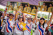 24 NOVEMBER 2012 - BANGKOK, THAILAND:  Women dance and hold up portraits of Bhumibol Adulyadej, the King of Thailand, during a large anti government, pro-monarchy, protest  on November 24, 2012 in Bangkok, Thailand. The Siam Pitak group, which sponsored the protest, cited alleged government corruption and anti-monarchist elements within the ruling party as grounds for the protest. Police used tear gas and baton charges againt protesters.       PHOTO BY JACK KURTZ