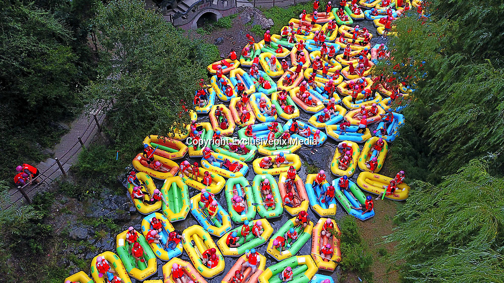 """SANMENXIA, CHINA - AUGUST 16: <br /> <br /> Hundreds of tourists drifting in the gorge<br /> <br /> Aerial view of tourists drifting in the gorge in summer, thus causing congestion on August 16, 2017 in Sanmenxia, Henan Province of China. Chinese """"dama"""" got their canoes into the riffle and danced to music to calm down tourists who were waiting anxiously. <br /> ©Exclusivepix Media"""