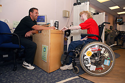 Access to services, Fitness instructor and disabled woman at the gym reception, Special desk lowered for wheelchair users,