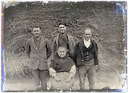 farmer with wife and sons posing in front of hay stack
