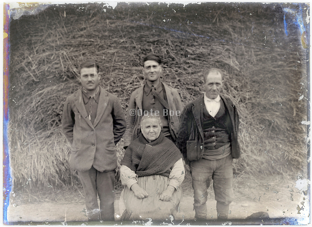 farmer with wife and sons posing in front of haystack