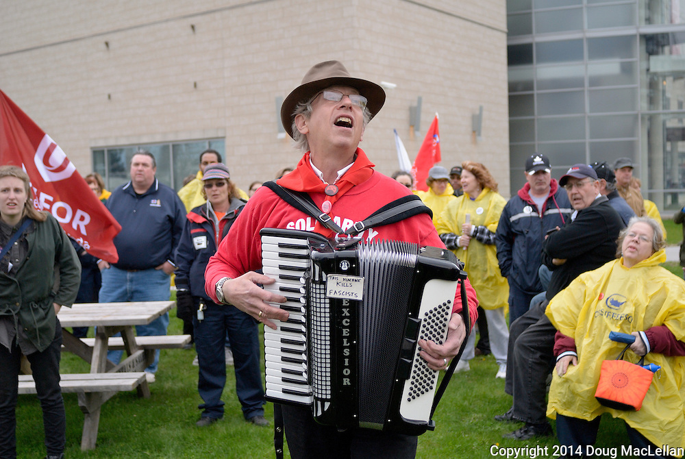 len Wallace is a local musian and academic who often performs labour oriented songs at public rallies such as this May Day march and rally.