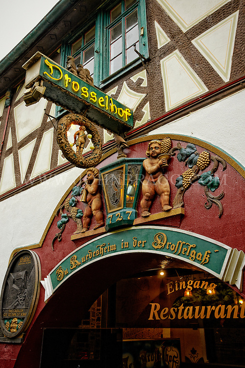 View of Cherub and Vine carvings outside a wine pub and restaurant on Drosselgasse, Rüdesheim, Germany.