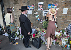 © Licensed to London News Pictures. 20/06/2017. London, UK. A jewish man looks on as a woman places a tribute with others near Finsbury Mosque in north London after a van ploughed into a crowd nearby. One person has been killed and 10 people are injured. Darren Osborne, 47, from Cardiff, continues to be held on suspicion of attempted murder and alleged terror offences.  Photo credit: Peter Macdiarmid/LNP