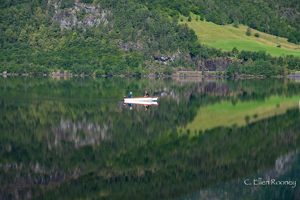 A small boat and reflections on still water on Granvinvatnet, Voss, Vestlandet, Norway, Europe
