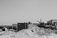 Observing a long and empty stretch of road toward the loyalist controlled town of Zliten, Libyan rebels on the watch at a frontline roadblock made of shipping containers and sand berms in Al Dafniyah, 25 km west of Misrata. 22 May 2011.