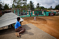 A boy watches batting practice for the Warriors baseball team from on top of the dugout at the municipal stadium on Thursday, February 25, 2010 in San Antonio de Guerra, Dominican Republic.